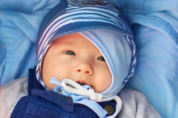 Adorable baby boy on a blue blanket, with a double protection of