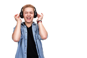 Young man in casual, trendy clothing listening to music and touc