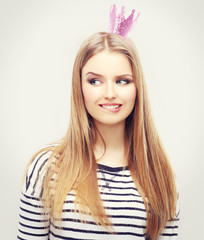Beautiful young girl  biting lips with festive pink crown on her