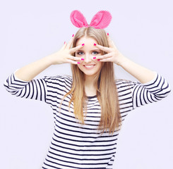 Beautiful young blond girl  pink ears on grey background
