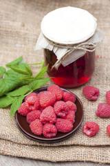 Raspberry preserve in glass jar and fresh raspberries on a plate