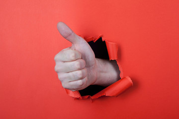 Make a thumb up sign by use his hands through hole on the red pa