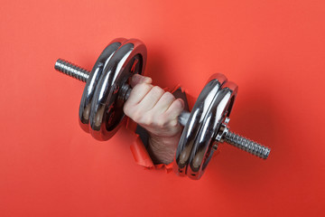 Hand holding chrome dumbbell through hole on the red paper.