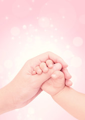 baby hand in hand of love with pink glitter background