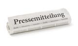 Zeitungsrolle mit der Überschrift Pressemitteilung