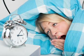 Junge Frau liegt schlaflos im Bett und gähnt