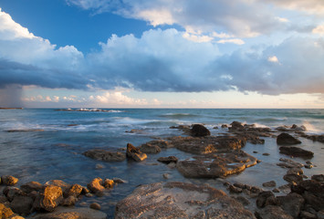 Low clouds above the stony shore of the sea. Seascape