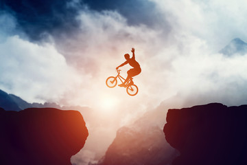 Man jumping on bmx bike over precipice in mountains at sunset. © Photocreo Bednarek