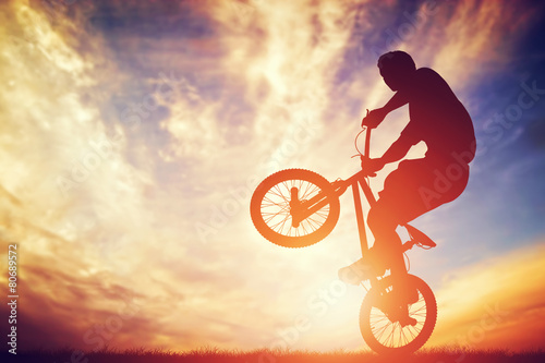 Fotobehang Extreme Sporten Man riding a bmx bike performing a trick against sunset sky