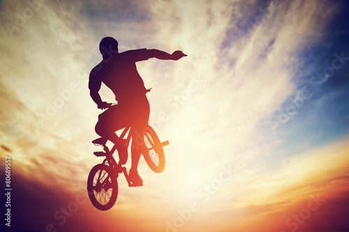 Poszter Man jumping on bmx bike performing a trick against sunset sky