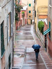 Man walking under the rain in a Genoa's alley