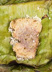 roasted immature beehive on banana leaves