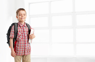 Boy with backpack and book