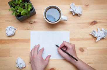 Blank notepad with pencil and coffee on wooden desk