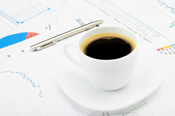 Coffee cup and calculator over some financial charts