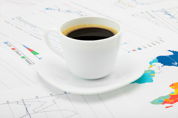 Coffee cup over some financial charts