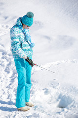 girl standing over hole with fishing rod and waiting for  catch