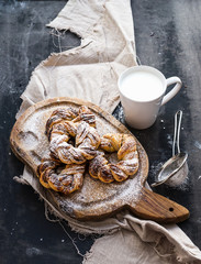Cinnamon buns with sugar powder on rustic wooden board