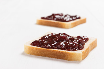 Two slices of bread with strawberry jam