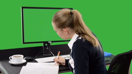 Businesswoman looking at monitor blank green screen and writing