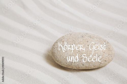 Leinwandbild Motiv Körper, Geist und Seele: Sand mit Stein und Text Hintergrund