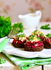 Canape from fried rye bread with beetroot,carrot,garlic and chee