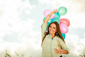 Girl holding balloons sky background