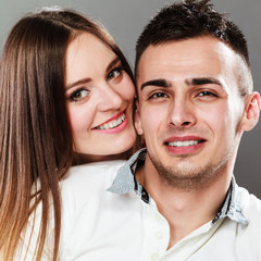 Smiling young couple portrait on gray