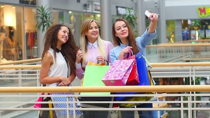 Group of happy best friends with shopping bags taking a selfie