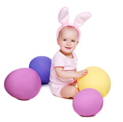 baby girl wearing rabbit ears sitting with giant easter eggs