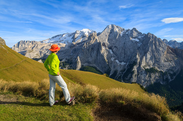 Woman tourist on hiking trail in Dolomites Mountains, Italy