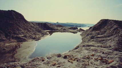 DOLLY MOTION: A small lake in the crater. Red sand land.
