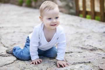 Cheerful little boy crawling on stone paved sidewalk