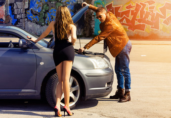 man repairing a car for sexy slim blonde girl