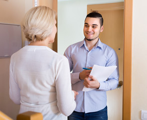 Mature woman and guy with papers at door