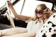 Young fashion blond woman in retro car