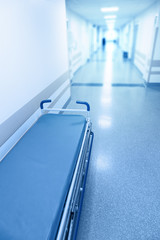 Long corridor in hospital with surgical gurney.