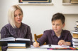 Young student learns at home with a his mom tutor. - 80707719