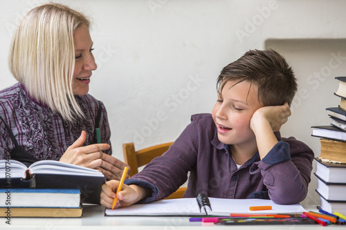 Junior student does homework with the help of his tutor.. - 80707744