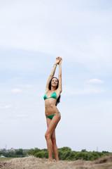 Young slim model in a green bikini