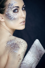 fashion portrait of pretty young woman with creative snake make