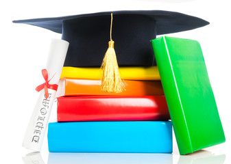 A mortarboard and graduation scroll, tied with red ribbon, on a