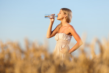 Woman drinking water in wheat field