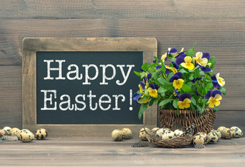Easter decoration with quail eggs, pansy flowers and vintage bla