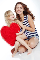 Mother with daughter with big red heart in studio