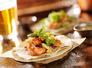 spicy shrimp avocado tacos in slanted composition