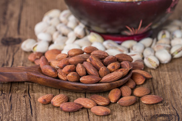 Almonds, pistachios and walnuts in wooden bowl