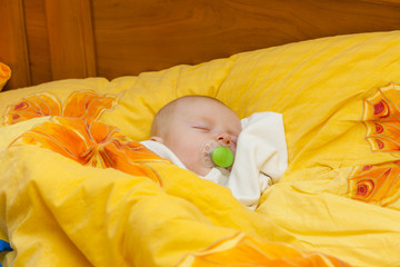 sleeping baby girl in big bed