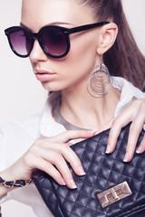 fashionable model in sunglasses and little black handbag