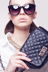 fashionable model in sunglasses and little black handbag